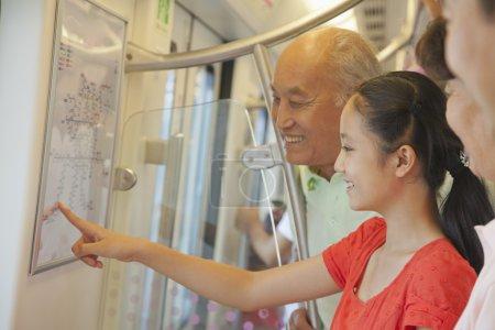 Photo pour Petite-fille avec grands-parents, debout dans le métro et en regardant la carte - image libre de droit