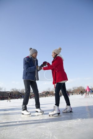 Photo for Young couple skating at ice rink - Royalty Free Image