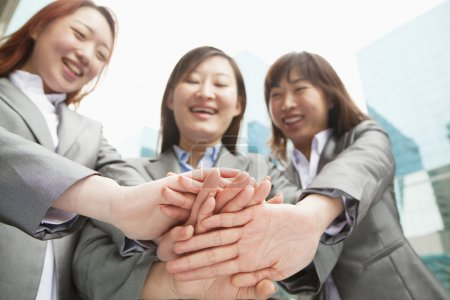 Photo for Three young businesswomen putting hands together, low angle view - Royalty Free Image