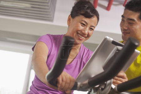 Woman exercising on the exercise bike with her trainer
