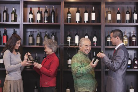 People Examining Wine Bottles at a Wine Store