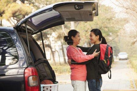 Photo pour Mère et fille embrassant derrière la voiture sur le campus du Collège - image libre de droit