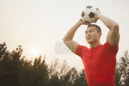 Mann wirft Fußball