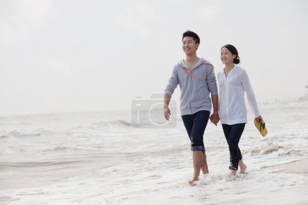 Couple walking by the waters edge on the beach