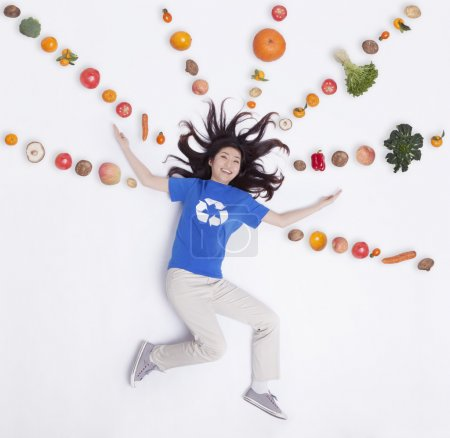 Photo for Young woman with fresh fruit and vegetables in lines and patterns, studio shot - Royalty Free Image
