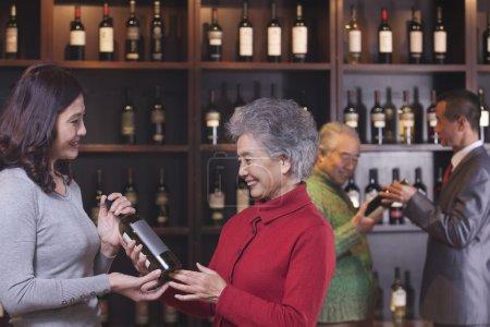 People Examining Wine Bottles