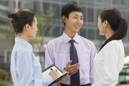 Photo for Three young business people talking outdoors, Beijing - Royalty Free Image
