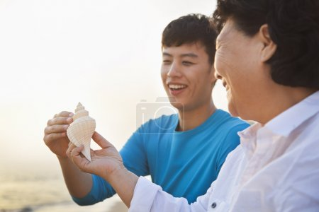 Grandmother and Grandson Looking At Seashell