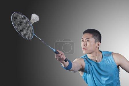 Photo pour Jeune homme jouant au badminton, frapper - image libre de droit