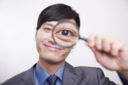 Photo for Young businessman looking through magnifying glass, studio shot - Royalty Free Image