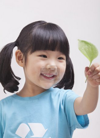 Girl looking at leaf, close up