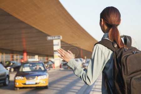 Traveler hailing a taxi at airport