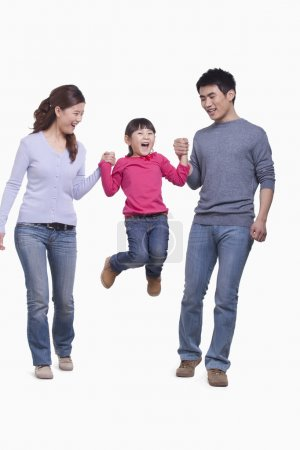 Family swinging child in mid-air