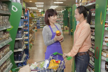 Sales clerk assisting woman in the supermarket