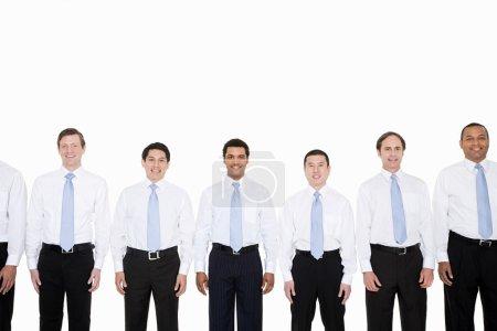 Similar looking businessmen in row