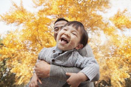 Photo pour Père et fils jouent dans le parc à l'automne - image libre de droit
