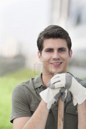 Photo pour Portrait de jeune homme souriant, tenant un râteau sur un toit-jardin supérieur dans la ville - image libre de droit