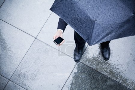 Businessman looking at his phone in the rain