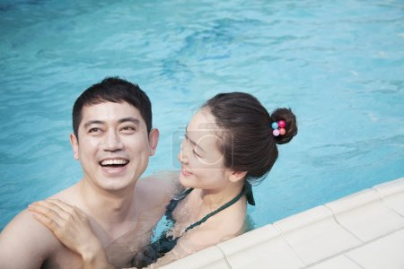 Сouple smiling and relaxing in the pool