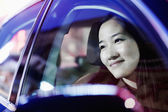 Smiling woman looking through car window