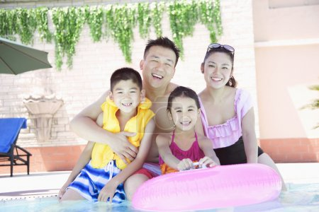 Family smiling by the pool