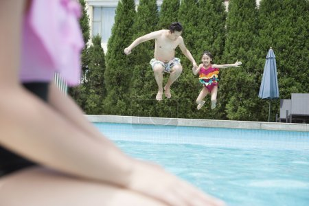 Father and daughter holding hands and jumping into the pool