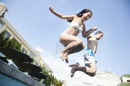 Two friends jumping into a pool
