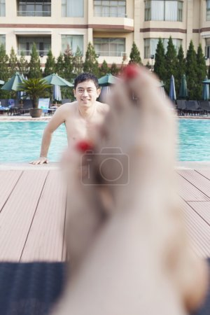 Woman's feet, man getting out of the water in the background