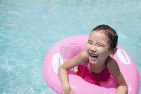 Girl swimming in the pool with a pink tube