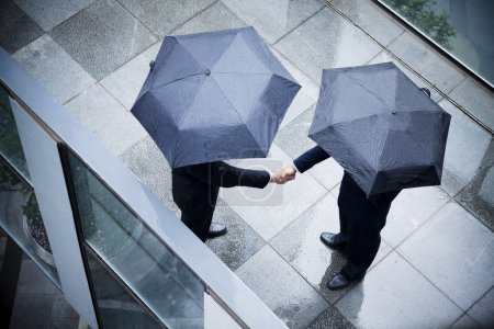 Businessmen shaking hands in the rain