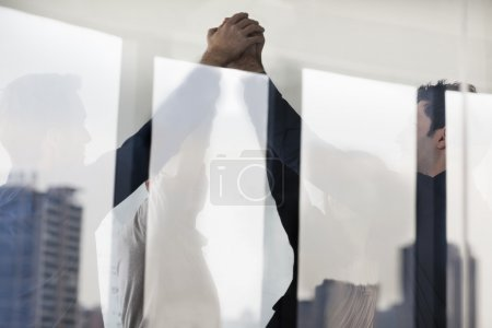 Photo for Four business people standing and cheering with hands together on the other side of a glass wall - Royalty Free Image