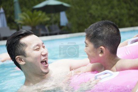 Father and son playing in the pool