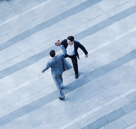 Photo for Aerial view of two businessmen giving each other a high five on the sidewalk - Royalty Free Image