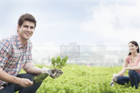 Man holding plant and gardening with young woman