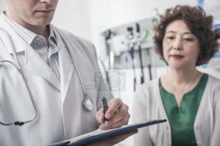 Doctor writing on medical chart with patient