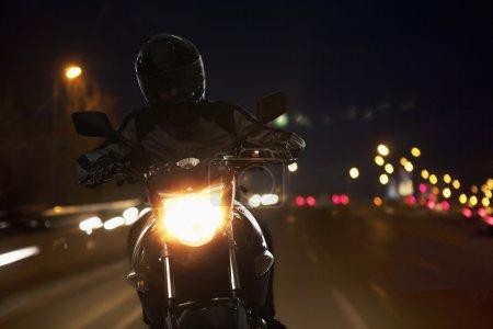 Man riding a motorcycle at night