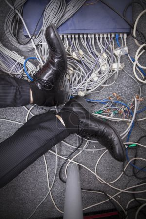 Businessman's feet surrounded by computer cables