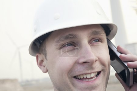 Photo for Young smiling male engineer in a hardhat on the phone beside a wind turbine, close-up - Royalty Free Image
