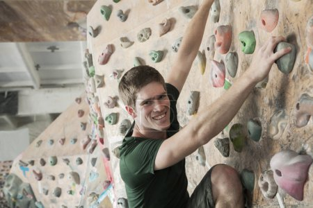 Man climbing up in an indoor climbing gym