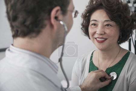 Doctor checking heartbeat of a patient