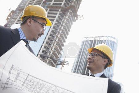 Photo pour Architectes regardant blueprint sur chantier, beijing - image libre de droit