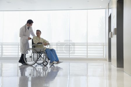 Doctor pushing patient in the hospital