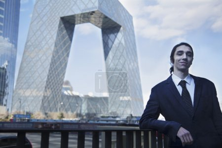 Businessman leaning on the railing with the CCTV building