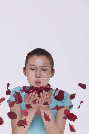 Woman blowing a handful of rose petals