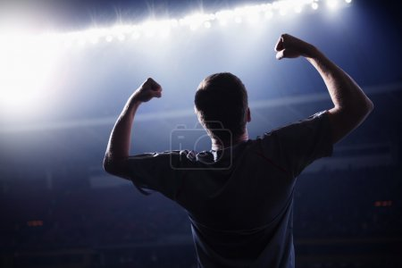 Photo for Soccer player with arms raised cheering, stadium at night time - Royalty Free Image