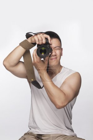 Man holding a camera and taking a photograph