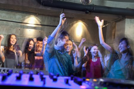 Photo pour Pont de DJ d'une foule dansant dans une boîte de nuit - image libre de droit