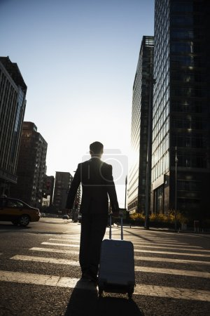 Businessman walking down the street with luggage