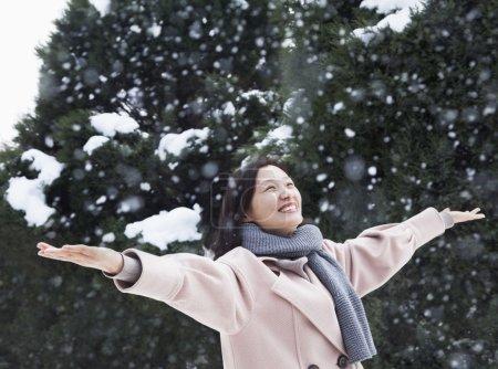 Photo pour Femme aux bras tendus à la sensation de la neige - image libre de droit
