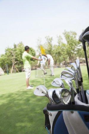 Foto de Tres amigos jugando al golf en el campo de golf, se centran en el carrito - Imagen libre de derechos